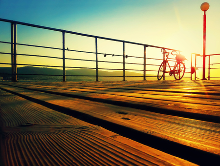 Silhouette of a bicycle on a seaside deck in the morning. Golden sunrise over the sea coast. Lifestyle background on the Sunny Beach, Nessebar, Bulgaria. Zdjęcie Seryjne