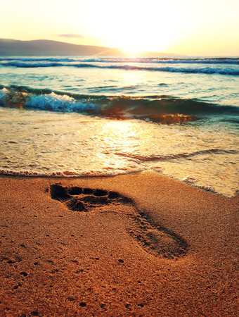 Human footprint in the beach golden sand in front of a sunrise over the sea. Zdjęcie Seryjne