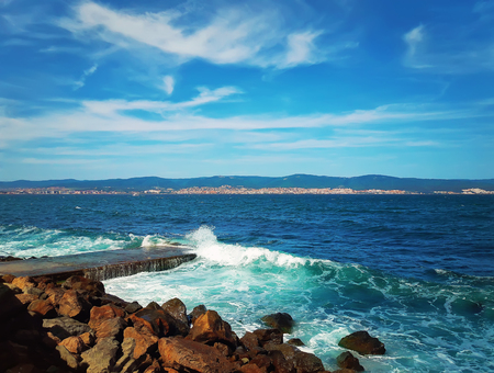Beautiful seashore landscape as the wavy blue sea and stone beach with a hills on the horizon. Nessebar, Bulgaria. Zdjęcie Seryjne
