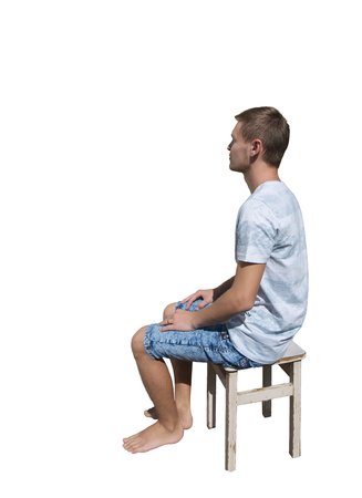 Side view full length portrait of pensive young man sitting on a chair and looking away isolated over white background. Zdjęcie Seryjne
