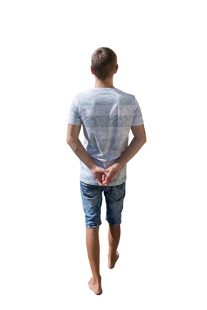 Rear view full length portrait of young man walking and stepping with hands behind his back isolated over white background. Zdjęcie Seryjne