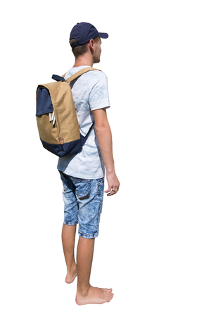 Side view full length portrait of a casual young man traveler carrying a backpack and wearing a cap ready for adventure isolated over white background.