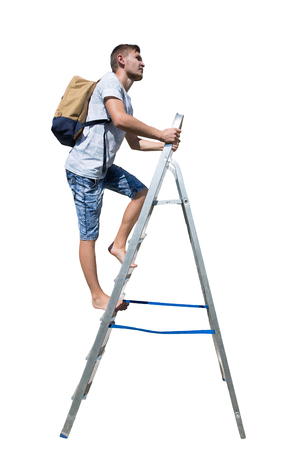 Side view full length portrait of a casual young man traveler climbing a ladder carrying a backpack looking away isolated over white background.