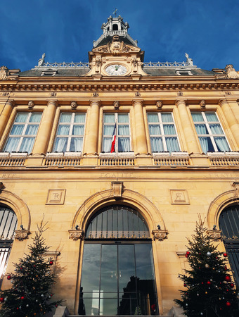 Outdoors view of the facade of Asnières-sur-Seine city hall building with two christmas on the each side of the entry. Sunny day beautiful blue sky northwestern suburbs of Paris, France.