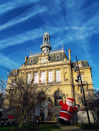 Outdoors view of the facade of Asnières-sur-Seine city hall building in the christmas period with santa balloon in the garden. Sunny day beautiful blue sky northwestern suburbs of Paris, France. Zdjęcie Seryjne