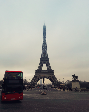 A red tourist bus on the pavement road in front of the famous Paris landmark Eiffel Tower view from the street. Zdjęcie Seryjne - 119620302