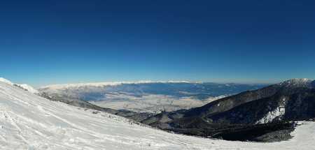 Panoramic view from the top of Pirin mountains to the Bansko city in Bulgaria. Cold winter day, snowy peaks and clear blue sky.