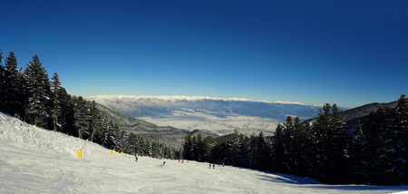 Bansko resort panoramic view with ski slope in the forest and snow trees, Bulgaria Zdjęcie Seryjne - 119620396