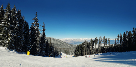 Panorama of snowy mountains in the winter season. Landscape ski trails with a blue sky on a clear day. Pirin peaks picturesque view of glaciers and rocky slopes.