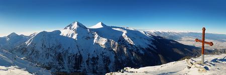 Cross on the top of Pirin mountains. Panorama of Todorka peak national resort clear blue sky in Bansko, Bulgaria.