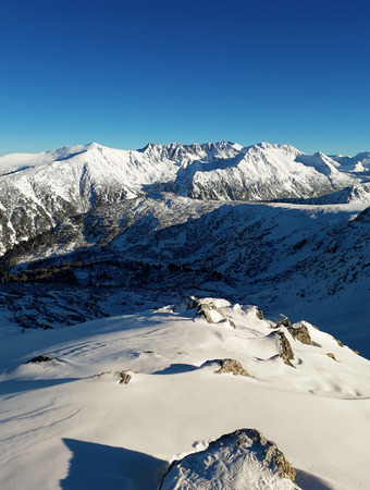 View from the top of Todorka Peak to the Pirin mountains ridge covered by snow in a sunny winter day with blue sky.