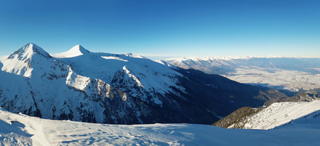 Panoramic view from the top of Pirin mountains to the ridge peaks. Cold snowy winter day and clear blue sky. Zdjęcie Seryjne