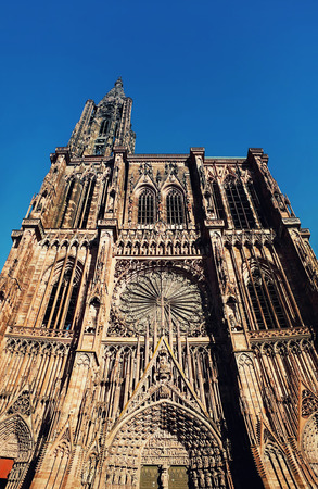 Main entrance of Roman Catholic Cathedral Notre Dame of Strasbourg in Alsace, France. Beautiful sunny day with clear blue sky. Majestic gothic architecture.