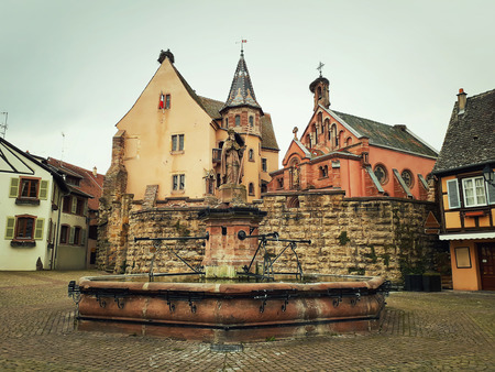 Castle, church and fountain named Saint Leon on the central square of Eguisheim village in Alsace, France. Imagens