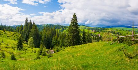 Picturesque spring Carpathians landscape panorama with an old hut in the forest and wooden split rail fence across a green and lush pasture on the valleys of Yablunytsya village, Ukraine. 스톡 콘텐츠