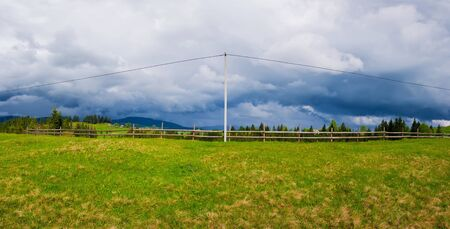 Electric power transmission pole in the mountains with cables along a wooden rail fence leading to the village. Panoramic landscape with a green field and cloudy sky background.