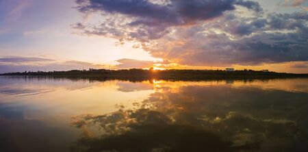 Wonderful sunset panorama over the city horizon with reflection on the calm lake water in a silent summer evening.