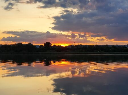 Beautiful sunset over the city horizon with reflection on the calm lake water in a silent summer evening. Zdjęcie Seryjne