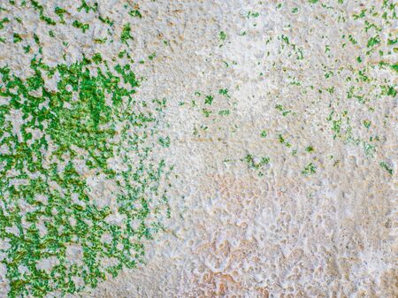 Abstract surface as green paint peeling off a concrete wall background. Old grungy, weathered painted construction structure. Cracked, dirty texture with plaster falling.