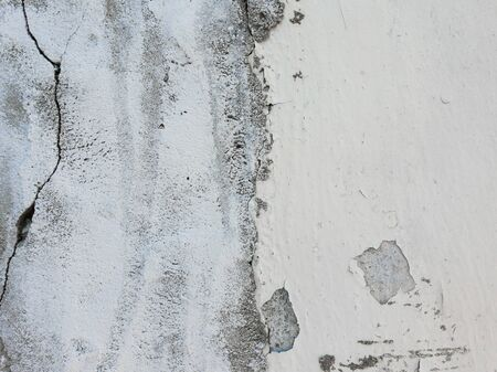 Old grungy, weathered concrete wall and cracked white paint peeling off the beton structure. Abstract construction element surface, dirty texture with plaster falling.