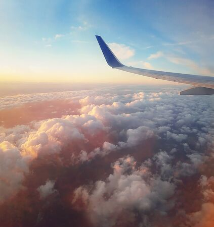 Aerial scene of a plane flight above the sunset colorful fluffy clouds. Airplane wing as seen through the window. Fly to the sky over the horizon. Travel concept, time for vacation relaxation.