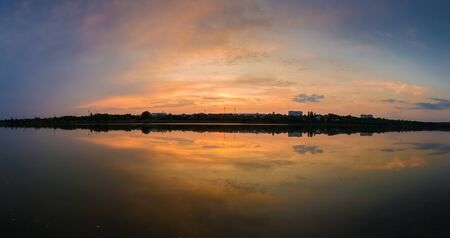 Panoramic view of colorful sunset clouds symmetric reflected on the lake surface. Idyllic summer evening, natural scene near a countryside pond with calm water.
