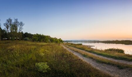 Rural panoramic landscape as a country road separates the lake from the forest. Beautiful evening scene, calm autumn background near a meadow of steppe vegetation. Stockfoto