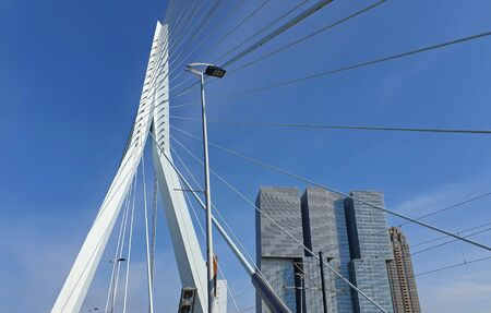 Erasmus bridge (The Swan) over Meuse river in Rotterdam, the Netherlands. Abstract architecture details over blue sky background.