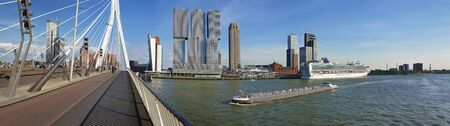Cityscape panorama from Erasmus bridge over Meuse river in Rotterdam, the Netherlands. Tall modern buildings on the horizon and big ships crossing the Erasmusbrug canal.