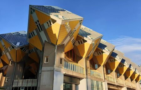 Cube houses under clear blue sky in Rotterdam, the Netherlands. Representing a village where each house is a tree. A row of quirky yellow unusual cube shape architecture apartment block.
