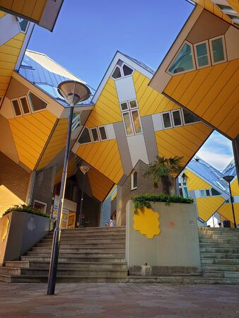 Cube houses under clear blue sky in Rotterdam, the Netherlands. Representing a village where each house is a tree. A lot of quirky yellow unusual cube shape architecture apartment block.