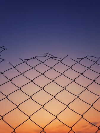 Old wire mesh fence texture against sunset sky background. Stockfoto