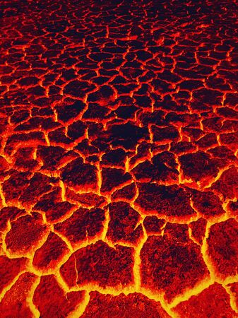 Heat red cracked ground texture burning after eruption volcano. Molten active lava texture background. Armageddon natural disaster or hell concept.