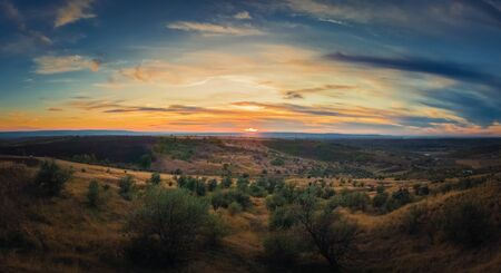 Soft autumn sunset panorama over countryside hills and valley. Beautiful rural landscape, nature scene.