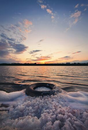 Fine art vertical shot, old vehicle tire thrown on the shore of a pond, covered with fluffy surf foam created by waves. Scenery landscape, peaceful sunset sky background over the city on the horizon.