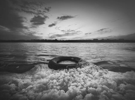 Old vehicle tire thrown on the shore of a pond, covered with fluffy surf foam generated by waves. Scenery sunset view, moody and dramatic background. Environment pollution and ecology concept.