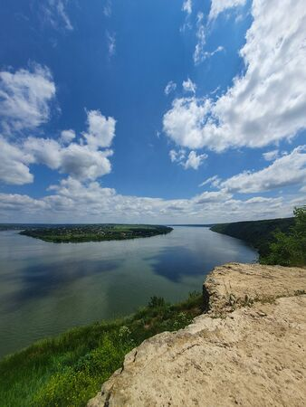 High angle, altitude view to the Nistru river, near Dubasari (Dubossary), Transnistria, Moldova. Idyllic vertical orientation scene on the peak of a cliff over the water under a rich blue sky.