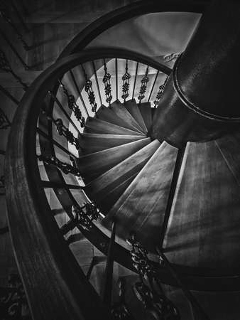 A look down to an old spiral staircase. Wooden circular stairway with ornate metallic railing, black and white vertical shot, interior architecture details of stair steps inside an ancient building.