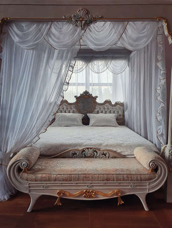 Ancient bedroom furniture style, medieval king bed, near the window, white curtains canopy and gold details. Close up background of a beautiful room luxuriously decorated for prince or princess.