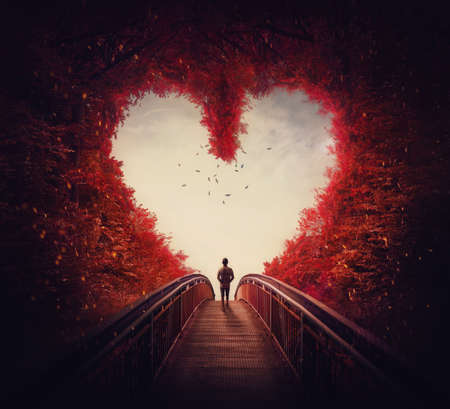 Follow your heart concept. A lone person lost in the autumn forest, found the way out of the woods, as walks a path through the heart shaped trees. Surreal and magic scene, red fall colors.