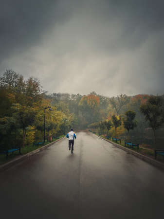 Single man running alone on an alley in the autumn park. Practicing sport outdoors in a rainy and misty day. Gloomy fall season mood. Healthy lifestyle workout jogging activity.