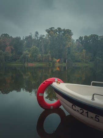 Moody autumn background with a boat on the calm lake water with a vibrant red lifeline ring. Colorful fall trees reflecting on the pond surface in a calm foggy day in the park. Cloudy gloomy sky. Stockfoto