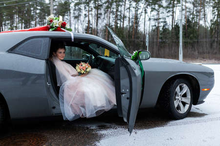 the bride and groom are sitting in a car decorated with flowers, the wedding cortege at the wedding ceremony, two happy people are going to get married Foto de archivo
