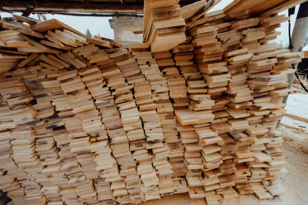 warehouse of wooden boards, background texture of wood harvested for shipment to the factory, finished products of the woodworking industry, many smooth bars of wood