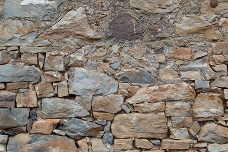 Photo of an ancient wall in Greece. Background of the old masonry. Vertical orientation.
