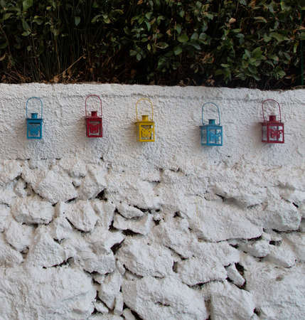 Photo of an old wall with a decor of multicolored lamps