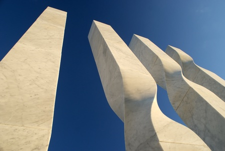 Abstract white marble monument in the background of blue sky