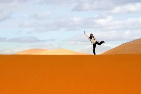 Sympatic woman balancing on the dunes in the Sahara desert