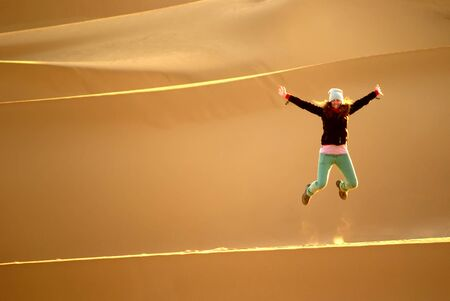 Happy woman leaping on the dunes in the Sahara desert