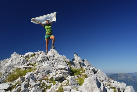 Hiker woman at mountain top summit holding a white scarf photo